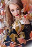 A mulher elegante 'sexy' bonita no revestimento preto com batom vermelho brilhante em seus bordos com composição brilhante anda n Fotografia de Stock Royalty Free