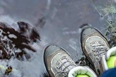 A mulher em botas de caminhada impermeáveis do turista está estando na água em uma poça imagem de stock royalty free