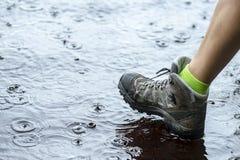 Mulher em botas de caminhada impermeáveis do turista que anda na água nas poças na chuva fotografia de stock