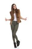 Mulher em calças caqui e em veste da pele que mostra os polegares acima Imagens de Stock Royalty Free