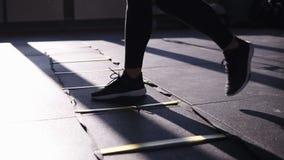 Mulher em caneleiras pretas que treina no gym ao pisar, saltando em seções divididas no exercício de assoalho que sua com video estoque