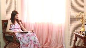 Mulher em casa que senta-se na cadeira na frente do livro de leitura da janela video estoque