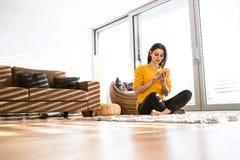 Mulher em casa que senta-se no tapete, guardando o telefone esperto, texting Fotos de Stock Royalty Free