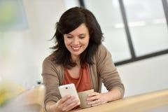Mulher em casa que usa o smartphone Fotos de Stock