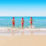 Mulher em chapéus do Natal na praia do mar Fotos de Stock Royalty Free