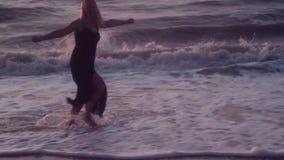 Mulher em corridas pretas do vestido ao seu espalhamento do lado braços para abraçar, no mar, ondas grandes vídeos de arquivo