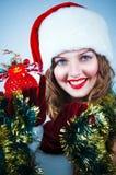 Mulher em e chapéu de Santa com uma esfera do Natal Fotografia de Stock Royalty Free