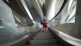 Mulher em escadas moventes na estação de trem vídeos de arquivo