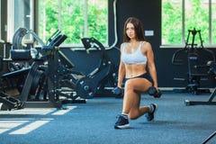 A mulher em esportes da forma veste o treinamento, fazendo investe contra o exercício com pesos no gym fotografia de stock royalty free