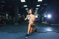 A mulher em esportes da forma veste o treinamento, fazendo investe contra o exercício no gym imagem de stock