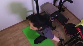 A mulher em fazer do banco do gym senta-se levanta em um pé vídeos de arquivo