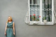 Mulher em Grey Dress Standing perto da casa Fotografia de Stock Royalty Free