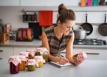 Mulher em ingredientes da lista da cozinha nas conservas vegetais imagem de stock royalty free