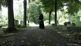 Mulher em lamentar a roupa preta que anda lentamente na aleia no cemitério filme