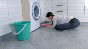 A mulher em luvas de borracha cor-de-rosa lava a mobília da cozinha com pano Assento no assoalho Vista lateral