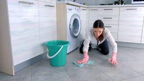 A mulher em luvas de borracha cor-de-rosa lava o assoalho da cozinha com um pano Telhas cinzentas no assoalho filme