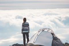 A mulher em nuvens nevoentas sozinhas do penhasco da montanha ajardina Fotos de Stock