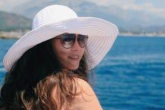 Mulher em ooks brancos grandes de um chapéu no mar Fotos de Stock