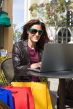 Mulher em oudoors da barra com sacos de compras que datilografa no vertica do portátil Imagem de Stock Royalty Free