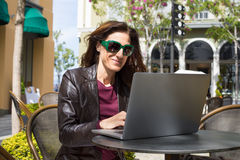 Mulher em oudoors da barra que datilografa no portátil Fotos de Stock Royalty Free