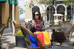 Mulher em oudoors da barra que olha o móbil com sacos de compras Fotos de Stock Royalty Free