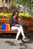 Mulher em oudoors do banco com sacos de compras que datilografa no portátil Foto de Stock Royalty Free