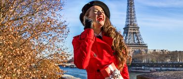 Mulher em Paris usando um telefone celular e guardando a caixa atual Fotos de Stock