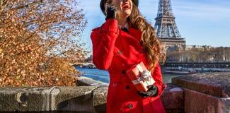Mulher em Paris usando um telefone celular e guardando a caixa atual Foto de Stock