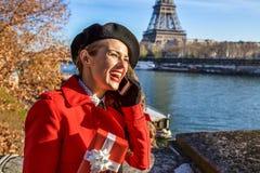 Mulher em Paris usando um telefone celular e guardando a caixa atual Imagens de Stock