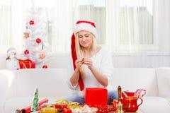 Mulher em presentes do Natal da abertura do chapéu de Santa Fotografia de Stock