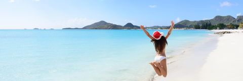 Mulher em Santa Hat And Bikini Jumping na praia imagem de stock