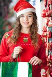 Mulher em Santa Hat Carrying Shopping Bag Fotografia de Stock Royalty Free
