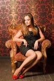 Mulher em sapatas vermelhas e no vestido que sentam-se na cadeira Imagem de Stock Royalty Free