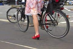 Mulher em sapatas vermelhas na bicicleta imagens de stock