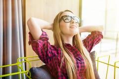 Mulher em seu trabalho, inclinando a para trás em uma cadeira com mãos em seus cabeça e olhos fechados, rmphasizing de pensar alg Fotos de Stock Royalty Free