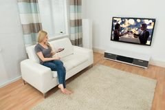 Mulher em Sofa Watching Movie Imagem de Stock Royalty Free