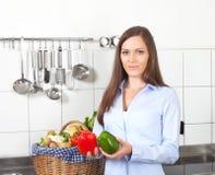 Mulher em sua cozinha com paprika vermelha e verde Imagem de Stock Royalty Free