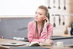 Mulher em sua cozinha que lê um livro Fotos de Stock