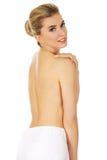 Mulher em topless do sorriso dos jovens com a toalha branca em torno de sua cintura Foto de Stock Royalty Free