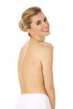 Mulher em topless do sorriso dos jovens com a toalha branca em torno de sua cintura Imagens de Stock Royalty Free