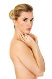 Mulher em topless nova que toca em sua cara Foto de Stock