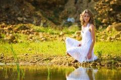 Mulher em um banco de rio imagem de stock