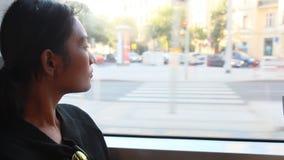 Mulher em um bonde que olha para fora a janela video estoque