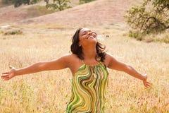 Mulher em um campo com braços abertos Imagens de Stock