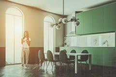 A mulher em um canto verde da sala de jantar arqueou janelas Fotos de Stock Royalty Free