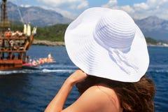 Mulher em um chapéu branco grande que está perto dos trilhos e dos olhares em Foto de Stock Royalty Free