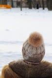 A mulher em um chapéu com pompon olha a neve Imagem de Stock Royalty Free