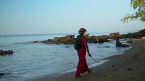A mulher em um chapéu de palha anda ao longo da praia Dia ensolarado na ilha de Phu Quoc Espaços abertos bonitos do oceano video estoque