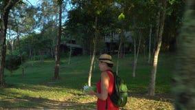 A mulher em um chapéu de palha na ilha em um jardim tropical A mulher de sorriso com o mapa Mulher atrativa nova com vídeos de arquivo