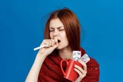 A mulher em um fundo azul guarda uma caneca e comprimidos, doença, doente, gripe, tosse foto de stock royalty free